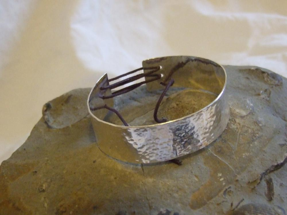 Silver textured bracelet with corset effect lace on the back