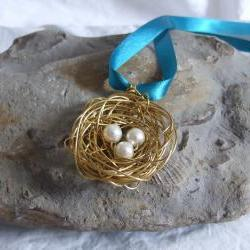 Brass Nest Pendant: A cute birds nest pendant made from wire with three white pearl bead eggs.